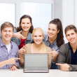 Smiling students pointing to blank lapotop screen — Foto Stock