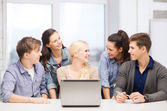 Smiling students with laptop at school — Stockfoto
