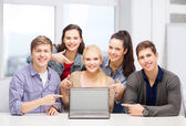 Smiling students pointing to blank lapotop screen — Stock Photo