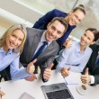 Business team showing thumbs up in office — Stock Photo #36778261