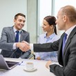 Two businessman shaking hands in office — Stock Photo #36779075
