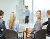 Businesswoman with team showing thumbs up — Stock fotografie