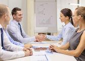 Empresário e empresária apertando as mãos — Foto Stock