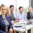 Businesswoman in office with team on the back — Stock Photo