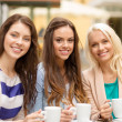 Three beautiful girls drinking coffee in cafe — Stock Photo