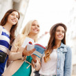 Three beautiful girls with tourist book in city — Stock Photo