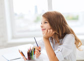 Little student girl drawing and dreaming at school — Stock Photo