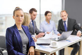 Businesswoman in office with team on the back — Stock fotografie