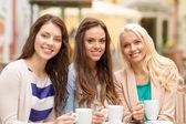 Three beautiful girls drinking coffee in cafe — Stock Photo