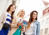 Three beautiful girls with tourist book in city — Stock fotografie