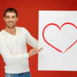 Handsome man holding big board with heart — Stock Photo
