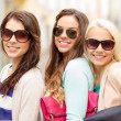 Stock Photo: Three smiling women in sunglasses with bags