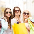 Three smiling girls with shopping bags in city — Stock Photo