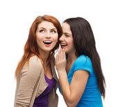 Two smiling girls whispering gossip — Stock Photo