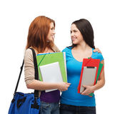 Two smiling students with bag and folders — Stock Photo