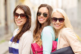 Three smiling women in sunglasses with bags — Stock Photo