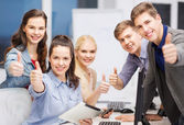 Students with computer monitor and tablet pc — Stock Photo