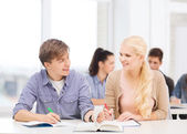 Two teenagers with notebooks and book at school — Foto Stock