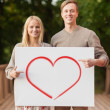 Romantic couple with white board and heart on it — Stock Photo