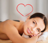 Beautiful woman in spa salon with hot stones — Stock Photo
