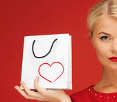 Lovely woman in red dress with shopping bag — Stock Photo