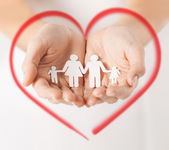 Womans hands with paper man family — Stock Photo
