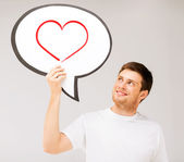 Smiling young man with text bubble and heart in it — Stock Photo