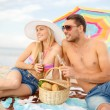 Smiling couple having picnic on the beach — Stock Photo