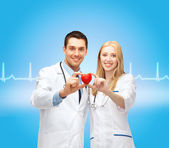 Smiling doctors cardiologists with heart — Stock Photo