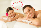 Smiling couple lying on massage table in spa salon — Stock Photo