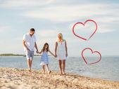 Happy family walking at the seaside — Stockfoto