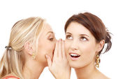 Two smiling women whispering gossip — Stock Photo