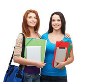 Two smiling students with bag, folders and tablet — Stock Photo