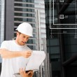 Male architect in helmet looking at blueprint — Foto Stock