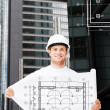 Male architect in white helmet with blueprint — Stock Photo