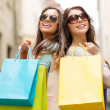 Two girls in sunglasses with shopping bags in ctiy — Stock Photo