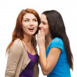 Two smiling girls whispering gossip — Stock fotografie #37137083