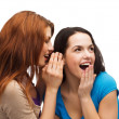 Two smiling girls whispering gossip — Foto de stock #37137209