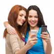 Stock Photo: Two smiling teenagers with smartphones
