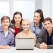 Smiling students with laptop at school — Stock Photo