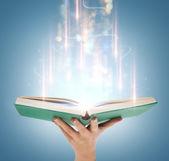 La mano sostiene un libro abierto con luces mágicas — Foto de Stock