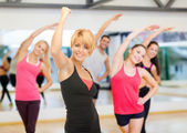 Group of smiling people exercising in the gym — Photo
