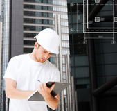 Male architect in helmet looking at blueprint — Stock Photo