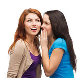 Two smiling girls whispering gossip — Stock Photo