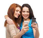 Two smiling teenagers with smartphones — Stock Photo