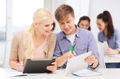 Two smiling students with tablet pc and notebooks — Foto Stock