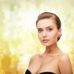 Woman wearing shiny diamond earrings and pendant — Stock Photo #37185343