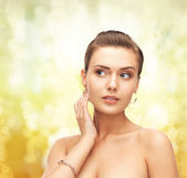 Woman wearing gold earrings and bracelet — Stock Photo
