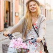 Attractive woman in hat with bicycle in the city — Stock Photo
