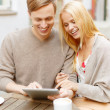 Stock Photo: Couple looking at tablet pc in cafe